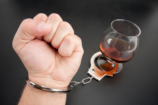 A hand locked to glass of alcohol by handcuffs