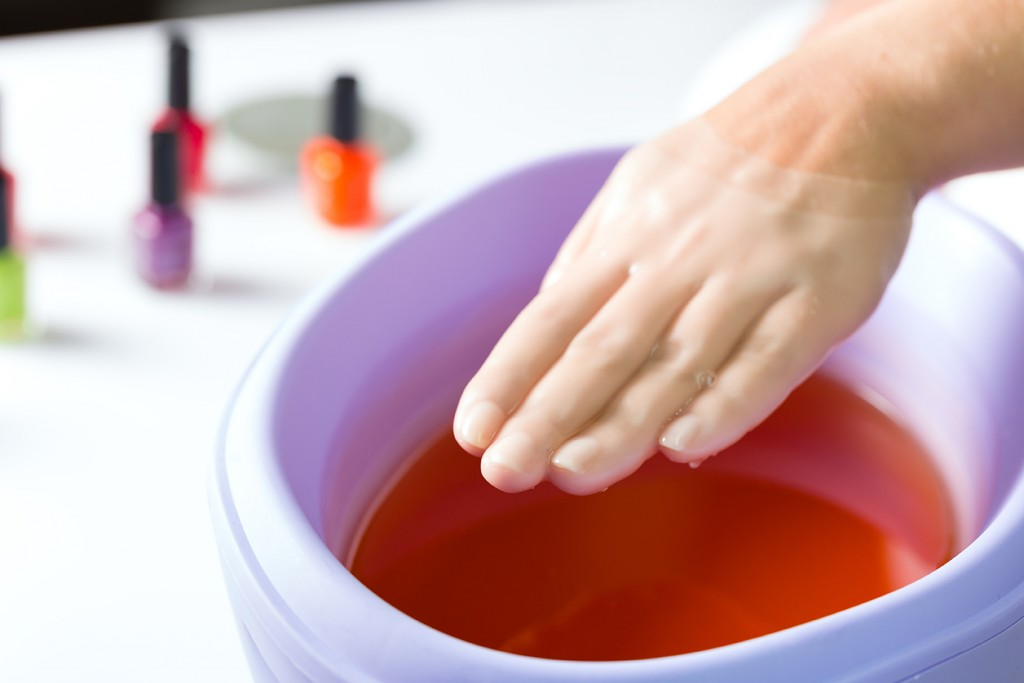 Woman in a nail salon receiving a manicure, she is bathing her hands in paraffin or wax