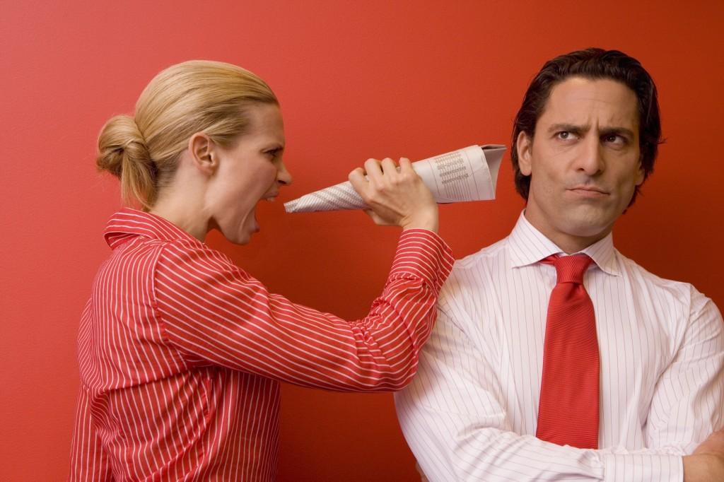 Businesswoman yelling in businessman's ear