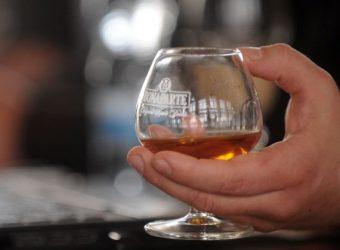 """Glāze ar alkoholisko dzērienu ražotāja AS """"Latvijas Balzams"""" ražoto brendija zīmola """"Bonaparte"""" dzērienu ar kanēļa garšu."""